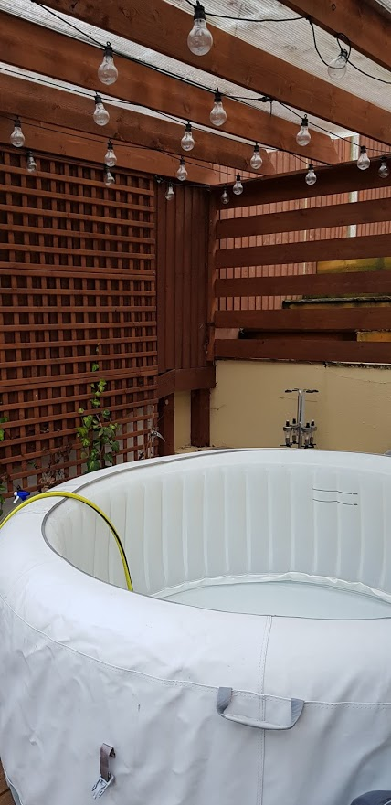 Hot tub under and wooden pergola, with lantern lights